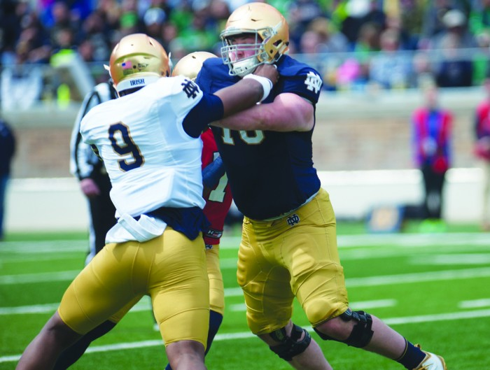 Irish sophomore defensive lineman Daelin Hayes, left, rushes the passer during the Blue-Gold game at Notre Dame Stadium on Saturday. Hayes had seven tackles and three sacks in the game.