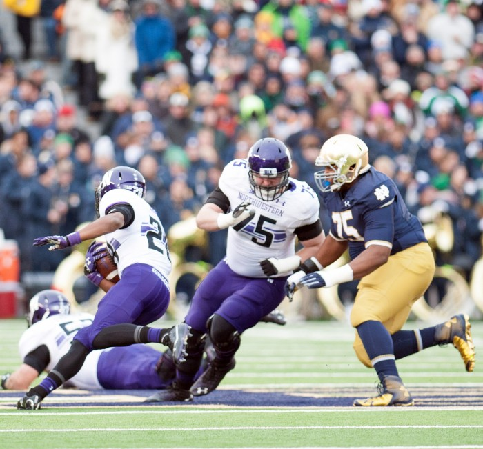Irish senior defensive lineman Daniel Cage pursues Northwestern senior running back Justin Jackson during Notre Dame's 43-40 loss to Northwestern at Notre Dame Stadium on Nov. 11, 2014.