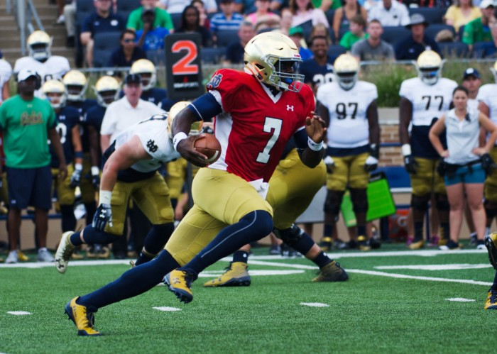 Irish junior quarterback Brandon Wimbush tucks the ball and scrambles from the pocket during Notre Dame's New and Gold scrimmage Sunday at Notre Dame Stadium.