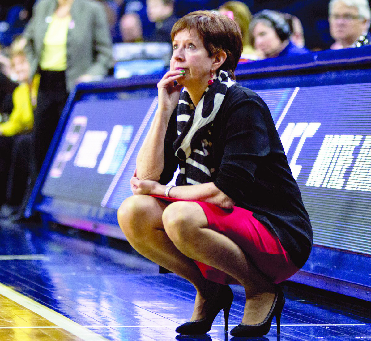 Irish head coach and Naismith Basketball Hall of Fame inductee Muffet McGraw crouches beside the court during Notre Dame's 88-82 overtime win over Purdue on March 19 at Purcell Pavilion.