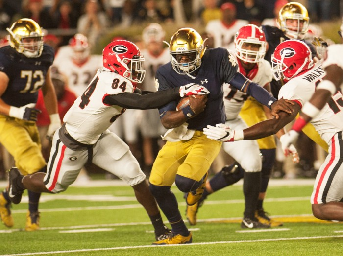 Irish junior quarterback Brandon Wimbush tries to fight his way through two Georgia defenders during Notre Dame's 20-19 loss to the Bulldogs on Saturday. Wimbush rushed 16 times for only one yard.