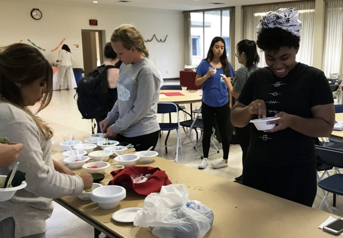 Students participate in the guacamole making contest at an event, hosted by Saint Mary's Latina culture club, La Fuerza, marking the beginning of Hispanic Heritage Month.