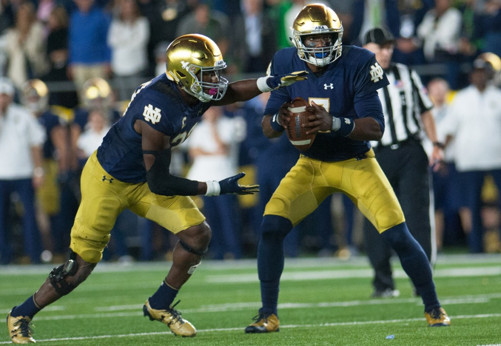 Irish junior running back Josh Adams, left, takes the handoff from junior quarterback Brandon Wimbush during Notre Dame's 49-14 win over USC on Saturday at Notre Dame Stadium.