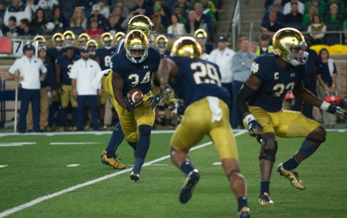 Irish sophomore running back Tony Jones Jr., left, takes a handoff and prepares to give it to sophomore wide receiver Kevin Stepherson, center, on the reverse during Notre Dame's 49-14 win over USC on Saturday at Notre Dame Stadium.